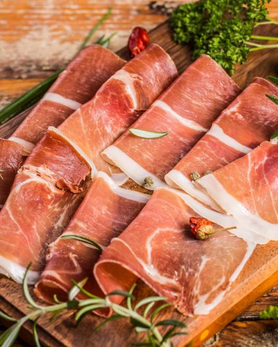 Slices of ham and herbs on a wooden table