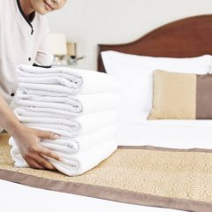 Close-up of maid in uniform bringing clean towels and putting it on the bed in the hotel room before guest's arrival